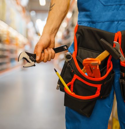 Male builder choosing tool belt at the shelf in hardware store. Constructor in uniform look at the goods in diy shop