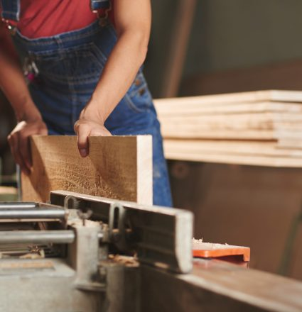 Close-up view of unrecognizable carpenter in denim overall processing wooden board on woodworking machine