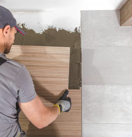 Caucasian Ceramic Tiles Installer at Work. Remodeling Bathroom Concept.