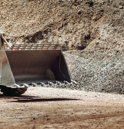 heavy construction machinery in open pit ore mine - wheel loader transports gravel at sorting plant