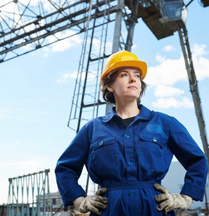 Waist up portrait of empowered woman working at construction site posing against sky with tower crane in background, copy space