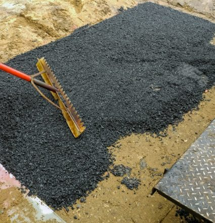 Worker on Asphalting paver machine during Road street repairing works