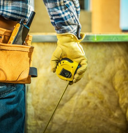 Construction Site Job. Worker with Measurement Tape in Hand and Wearing Tools Belt. Industrial Theme.
