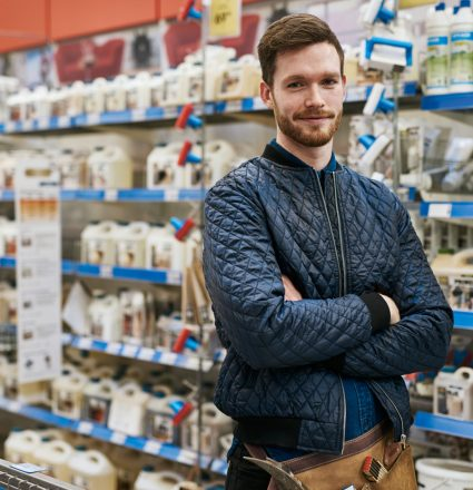 Confident handyman in a hardware store standing amongst the racks of products with folded arms smiling at the camera