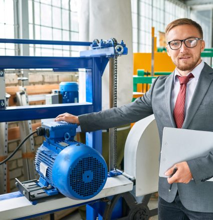 Portrait of successful salesman wearing suit posing looking at camera, standing by machine tools in industrial showroom