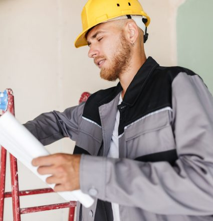 Engineer in work clothes and yellow hardhat dreamily looking on plan of new apartments leaning on red ladder at work