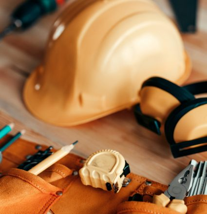 Carpentry tools and protective equipment on the desk in woodwork workshop, selective focus