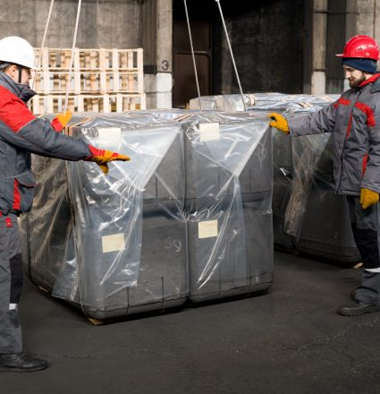 Full length portrait of two factory workers  packaging shipment units in industrial workshop, copy space
