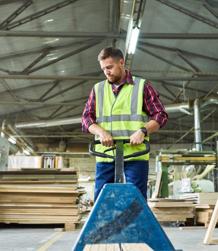 Portrait of young man wearing reflective jacket pulling cart in factory warehouse, copy space